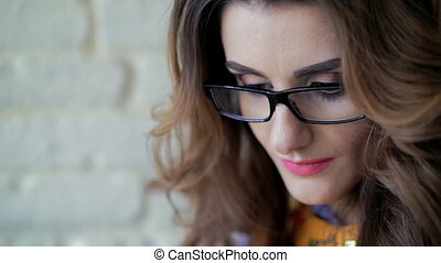 Close up face of sincere lady in glasses calling and smiling