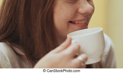Close-up face of young beautiful schoolgirl, drinking coffee from a cup.