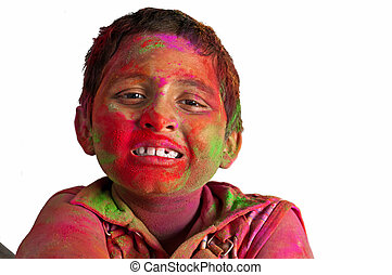Close up face of young boy playing Holi, smiling with colors...