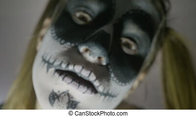 Close up face of young girl wearing halloween skull paint...