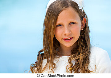 Close up face shot of cute communion girl against blue background.