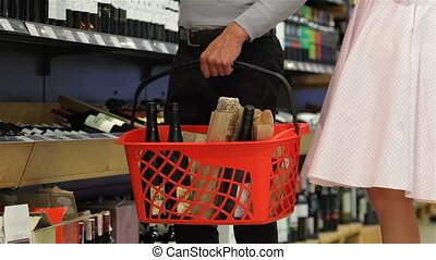 Close-up family couple choosing bottle wine