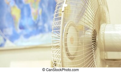close-up. Fan conditioner rotating. on the background of a blurred map of the world hanging on the wall.