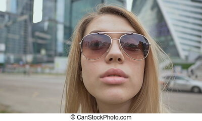 Close up fashion and glamour beautiful woman portrait wearing sunglasses. A girl with lush lips against the background of the city center.