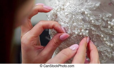Close-up fashion designer for brides in his Studio pins needles lace wedding dress. Seamstress creates an exclusive wedding dress. Secure with pins and needles outline. Small private business.
