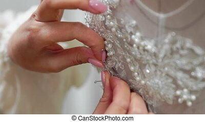 Close-up fashion designer for brides in his Studio pins needles lace wedding dress. Seamstress creates an exclusive wedding dress. Secure with pins and needles outline. Small private business. Sew rhinestones and crystals to the dress thread and needle. Jewelry work.
