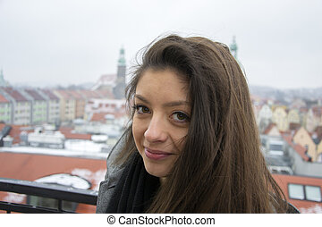 Close-up Fashion woman portrait of young pretty trendy girl posing at the city in Europe, summer winter fashion, holding her hair smiling to camera portrait. trendy