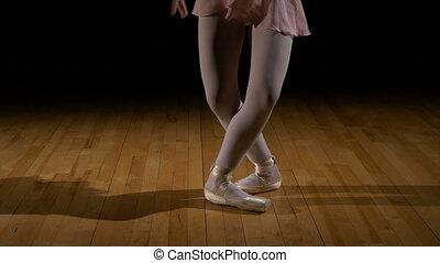 Close up feet of a ballerina doing jumps in ballet dancer shoes
