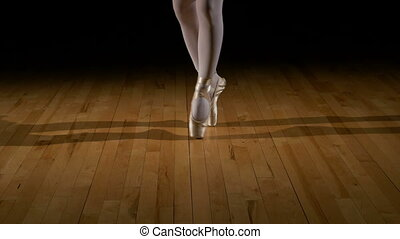 Close-up feet of a dancing ballerina wearing pointes shoes