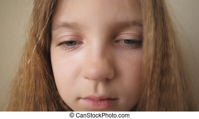 Close up female face of desperate child looking into camera indoor. Disappointed gaze of small upset kid. Portrait of little blonde girl with sorrowful expression inside.