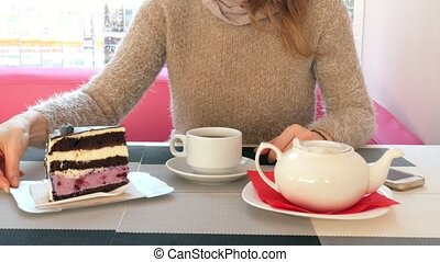 Close-up female hand stroking the cup of tea in cafe. Woman in restaurant with hot beverage and cake