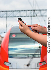 close-up, female hand with a mobile phone at railway station