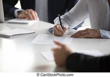 Close up female hands affirming contract with signature during m
