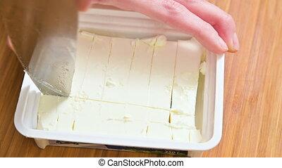 Close-up female hands cut tofu cheese in plastic packaging...