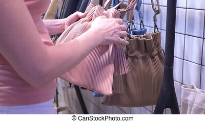 close-up, female hands. girl chooses a bag in the mall