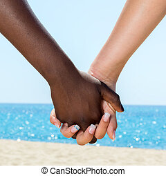 Close up female hands holding each other outdoors.