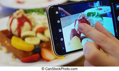 close-up. Female hands take a picture of a dessert of Viennese waffles, ice cream and fresh fruit on a smartphone in a restaurant.