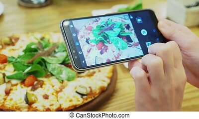 close-up. Female hands take photo of pizza on smartphone in...