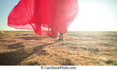 close-up female Slender legs in sandals in a red loose transparent dress that flutters in the wind in waves goes on dry grass in nature. Low angle slow motion. Backlight with glare.