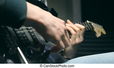 Close up fingers of guitarist at the strings. Mens arms...