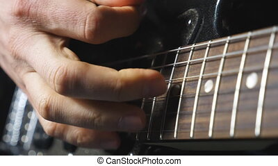 Close up fingers of guitarist strumming the strings. Hand of...