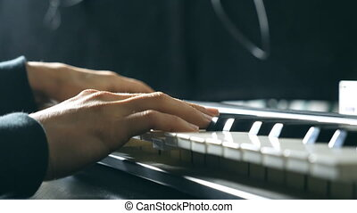 Close up fingers of pianist at the piano keys. Mens arms...