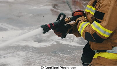 Close up, firefigter extinguish fire with the hose. High quality 4k footage