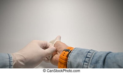 Close-up first-person view men's hands in a blue denim shirt and a watch with a yellow strap on their right hand wear protective rubber medical gloves and show a thumbs up gesture. Instructions for the proper use of virus prevention measures and pandemic control.