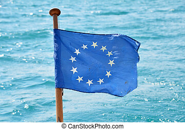 Close up flag of EU waving in wind over sea water