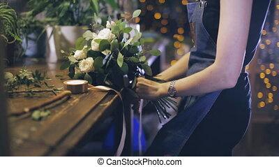 Close-up. florist making bouquet at flower shop