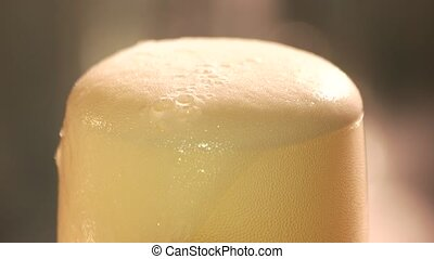 Close up foam leaking out of glass of beer. Top of frosty...