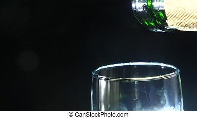 close-up, foaming champagne in a glass on a black background. 4k, slow motion