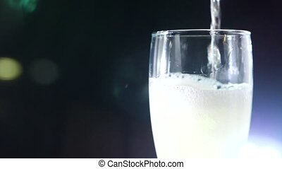close-up, foaming champagne in a glass on a black background. slow motion