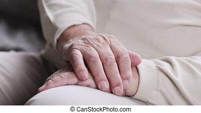 Close up focus on mature older male folded wrinkled hands. ...