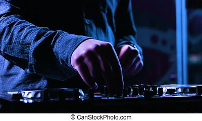 Close-up footage of a male music artists hands pushing pads and scratching on a control desk, DJ mixing music at nighclub.