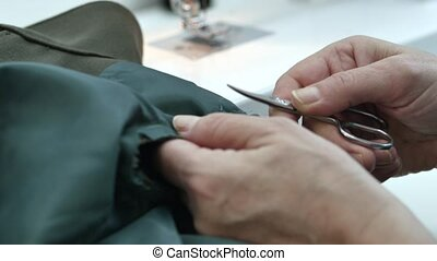 Close up footage of a professional woman tailor is ripping...