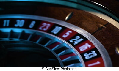 Close-up footage of a small white ball gets into a slot in a russian roulette wheel.