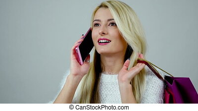 Close-up footage of a young cheerful woman answers to a call on cell phone and has a talk about her shopping.
