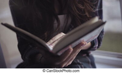 Close-up footage of an attractive caucasian girl reads a book,  panoramic shot.
