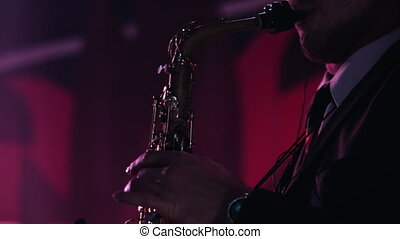 Close-up footage of caucasian man playing saxophone at nightclub.