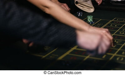 Close-up footage of hands of adult people placing their bets on a roulette table in casino
