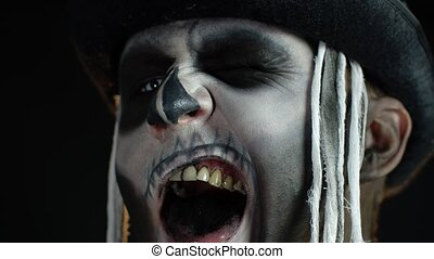 Close up footage of sinister man face with horrible Halloween skeleton makeup. Guy making faces, showing black teeth, trying to scare. Horror theme. Day of The Dead. Dark background. 6k downscale