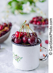 Close up Fresh cherry fruit in white mug, other dishes with berries and vase with jasmine flowers on the light marble table. Soft selective focus. Summer countryside concept