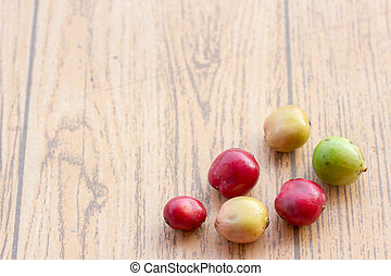 fresh coffee beans on wood table,red fruit with caffeine addiction.
