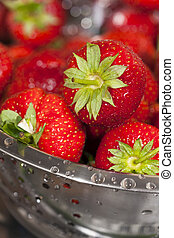 Close-up fresh strawberries in a stainless steel colander