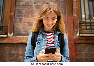 Close up front of smiling young woman looking at mobile phone in city