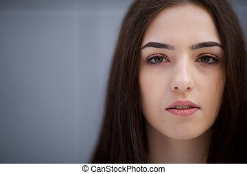 front portrait of beautiful young woman with serious expression on face