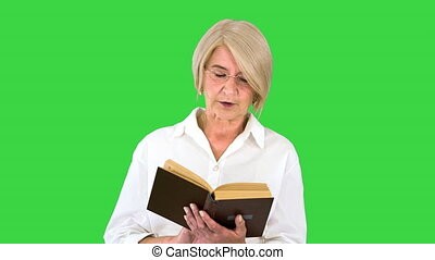 Close up. Front view. Beautiful senior woman reading aloud from a book on a Green Screen, Chroma Key. Professional shot in 4K resolution. 063. You can use it e.g. in your medical, commercial video, business, presentation, broadcast