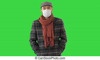 Gentleman with medical face mask walking on a Green Screen, Chroma Key.
