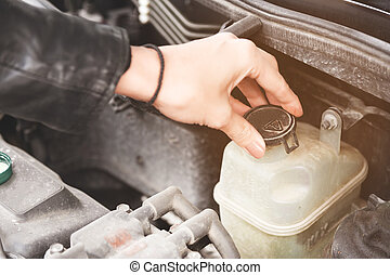 Close up girl checks the level of coolant in the engine of her car